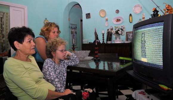 Dos mujeres y un niño observan hoy, domingo 7 de marzo del 2010, en La Habana, en el horario estelar de la televisión estatal cubana, la serie