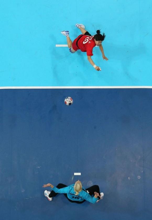 La surcoreana Jihae Jung lanza un penalti a la danesa Christina Pedersen durante el partido de la fase preliminar del Grupo B de balonmano. Foto: RICHARD HEATHCOTE (GETTY IMAGES)