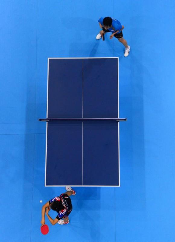 La surcoreana Kim Kyungah (abajo) durante la competición femenina de tenis de mesa contra Feng Tianwei de Singapur. Foto:  SAEED KHAN (AFP)